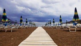 Stühle und Regenschirme auf dem Strand vor dem Sturm Lizenzfreies Stockbild