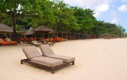 Stühle und Regenschirme auf Strand Lizenzfreie Stockbilder