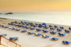 Stühle und Regenschirme auf Strandurlaubsort in Griechenland stockbild