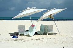 Stühle und Regenschirme am Strand Stockfotos