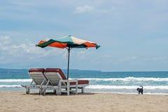 Stühle und Sonnenschirm auf Strand mit blauem Ozean lizenzfreie stockfotos