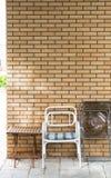 Stühle und Tabelle vor einer Backsteinmauer Lizenzfreie Stockbilder