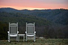 Stühle und Tabellen-übersehenhügel am Sonnenuntergang lizenzfreies stockfoto