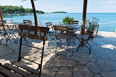 Stühle und Tabellen mit schöner Seeansicht Lizenzfreie Stockfotos