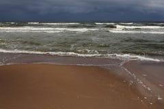Stürmische Meereswellen, dunkelblauer Himmel und Sand Stockfoto