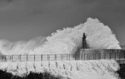 Stürmische Welle über altem Leuchtturm und Pier von Viavelez stockbild