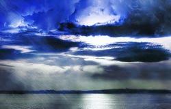 Stürmische Wolken über See Stockbild