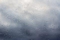 Stürmische Wolken durch das nasse Fenster Lizenzfreie Stockbilder