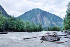 Stürmischer Fluss, der in der Dämmerung zwischen die Berge fließt Stockfotografie