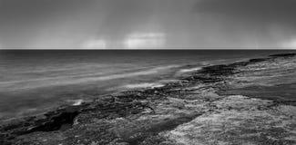 Stürmischer Himmel über dem Ozean mit entferntem Blitzschlag Stockfotografie