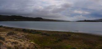 Stürmischer Himmel über ruhiger Wasserlandschaft Lizenzfreie Stockbilder