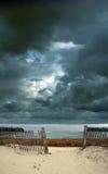 Stürmischer Himmel am Strand mit Zaun Lizenzfreies Stockfoto