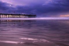 Stürmischer Sonnenuntergang mit Pier und Leuchten 2 Stockbild