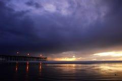 Stürmischer Sonnenuntergang mit Pier und Leuchten Stockfotos