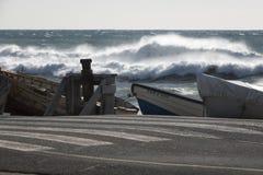 Stürmisches Meer mit den Booten festgemacht nahe der Straße lizenzfreies stockfoto