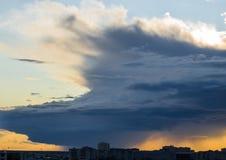Stürmisches Supercellwetter über der Stadt bei Sonnenuntergang Lizenzfreie Stockbilder