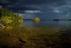 Stürmisches weater über dem See, kleine sonnige Insel stockfotografie