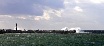 Stürmisches Wetter am Pier mit Leuchtturm Lizenzfreie Stockfotografie