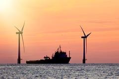 Stützbare Betriebsmittel Windpark mit Schiffsschattenbild am tropica lizenzfreies stockfoto