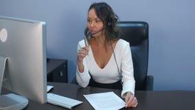Stützen Sie Telefonbetreiber im Kopfhörer, der mit Laptop im Büro arbeitet stock footage
