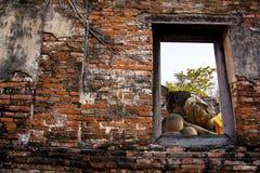 Stützender Buddha hinter altem Ziegelsteinfenster bei Wat Phutthaisawan, Stockbild