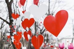St华伦泰装饰在公园 红色和白色手工制造心脏 免版税图库摄影
