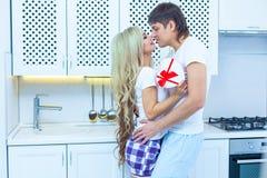 St华伦泰` s天爱 2月14日 英俊年轻人给当前美丽的妇女在家在厨房里 免版税库存照片