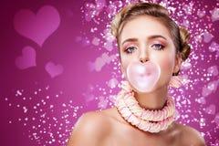 St华伦泰` s日 吹从泡泡糖的画象美丽的年轻性感的白肤金发的女孩桃红色心脏 红色假日 免版税库存图片