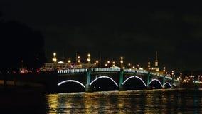 ST ΠΕΤΡΟΥΠΟΛΗ, ΡΩΣΙΑ: Κυκλοφορία αυτοκινήτων στη φωτισμένη γέφυρα τριάδας στη νύχτα απόθεμα βίντεο