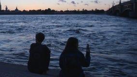 ST ΠΕΤΡΟΥΠΟΛΗ, ΡΩΣΙΑ: Νέο ζεύγος σε ένα ανάχωμα του ποταμού Neva κοντά στη γέφυρα Troitsky σε ένα σούρουπο απόθεμα βίντεο