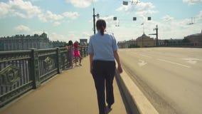 ST ПЕТЕРБУРГ - РОССИЯ - 7-ОЕ ИЮНЯ Женщина 2019 полици идет вдоль моста реки акции видеоматериалы