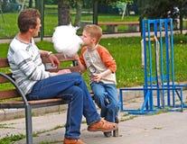 ST 彼得斯堡俄国 有儿子的父亲在公园吃在一条长凳的棉花糖 免版税库存照片
