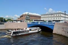 ST 彼得斯堡俄国 游览船漂浮在蓝色桥梁下通过Moika河在夏日 免版税库存照片