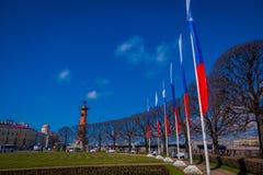 ST 彼得斯堡,俄罗斯, 2018年5月01日:与旗子的南有船嘴装饰的专栏连续接近在唾液的交换大厦  图库摄影
