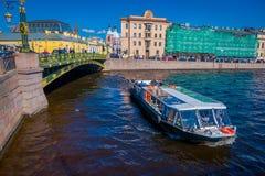 ST 彼得斯堡,俄罗斯, 2018年5月02日:室外观点的一yatch的游人接近沿Moyka河的绿色桥梁 图库摄影
