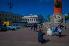 ST 彼得斯堡,俄罗斯, 2018年5月01日:拍照片的爸爸对他的在有船嘴装饰的专栏前面的孩子在历史城市 免版税库存照片