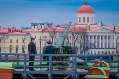 ST 彼得斯堡,俄罗斯, 2018年5月17日:未认出的有老火炮的人佩带的制服室外看法开枪近 免版税库存照片