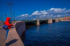 ST 彼得斯堡,俄罗斯, 2018年5月02日:的未认出的人穿一件红色夹克和钓鱼在桥梁的室外观点 免版税库存图片
