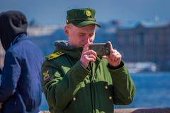 ST 彼得斯堡,俄罗斯, 2018年5月01日:穿有一个圆环的俄国人军服在他的手上,拍一张照片与 免版税库存图片