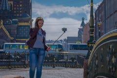 ST 彼得斯堡,俄罗斯, 2018年5月01日:穿温暖的衣裳的白肤金发的俄国妇女采取使用她的selfiestick selfied的  免版税图库摄影