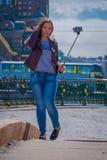 ST 彼得斯堡,俄罗斯, 2018年5月01日:穿温暖的衣裳的白肤金发的俄国妇女采取使用她的selfiestick selfied的  免版税库存图片