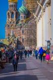 ST 彼得斯堡,俄罗斯, 2018年5月02日:走在接近一个街市的边路的未认出的人民与教会 库存照片