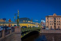 ST 彼得斯堡,俄罗斯, 2018年5月02日:走在沿Moyka的一座绿色桥梁的室外观点的未认出的人民 免版税库存照片
