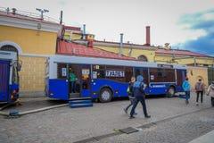 ST 彼得斯堡,俄罗斯, 2018年5月17日:走接近在停车处的公共汽车的室外观点的未认出的人民在St 免版税库存图片