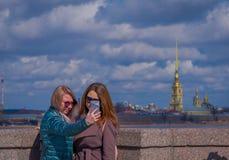 ST 彼得斯堡,俄罗斯, 2018年5月01日:采取与华美的彼得的室外观点的两名美丽的俄国妇女一selfie 免版税库存照片