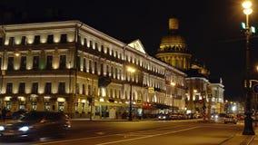 ST 彼得斯堡,俄罗斯:在一条街道上的汽车通行沿大厦和以撒的大教堂夜 股票录像
