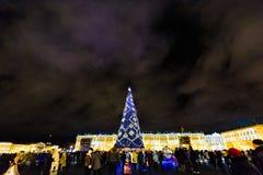 ST 彼得斯堡,俄罗斯- 2016年12月25日:在宫殿正方形,新年之前装饰的夜城市的圣诞树 男孩节假日位置雪冬天 免版税图库摄影