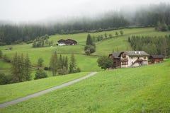 ST 马格达莱纳,意大利- 2015年9月14日:绿色牧场地围拢的一多云mornig的传统房子 免版税库存照片