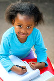 Söt afrikansk studenthandstil i anteckningsbok på skrivbordet Royaltyfri Bild