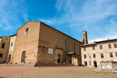 St. Agostino Church - San Gimignano Italy. Church of Sant`Agostino St. Augustine in Romanesque and Gothic style 1298 and an old water well - San Gimignano, Siena Royalty Free Stock Image